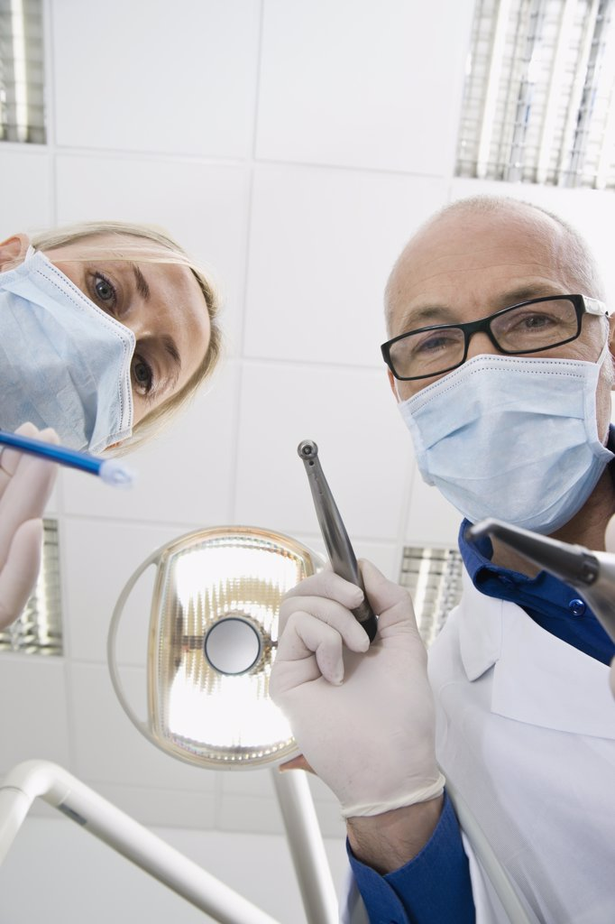 Stock Photo: 1570R-128012 View from below of a dentist and an assistant holding dental tools