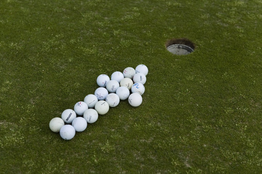 Arrow of golf balls pointing to a hole on a putting green : Stock Photo