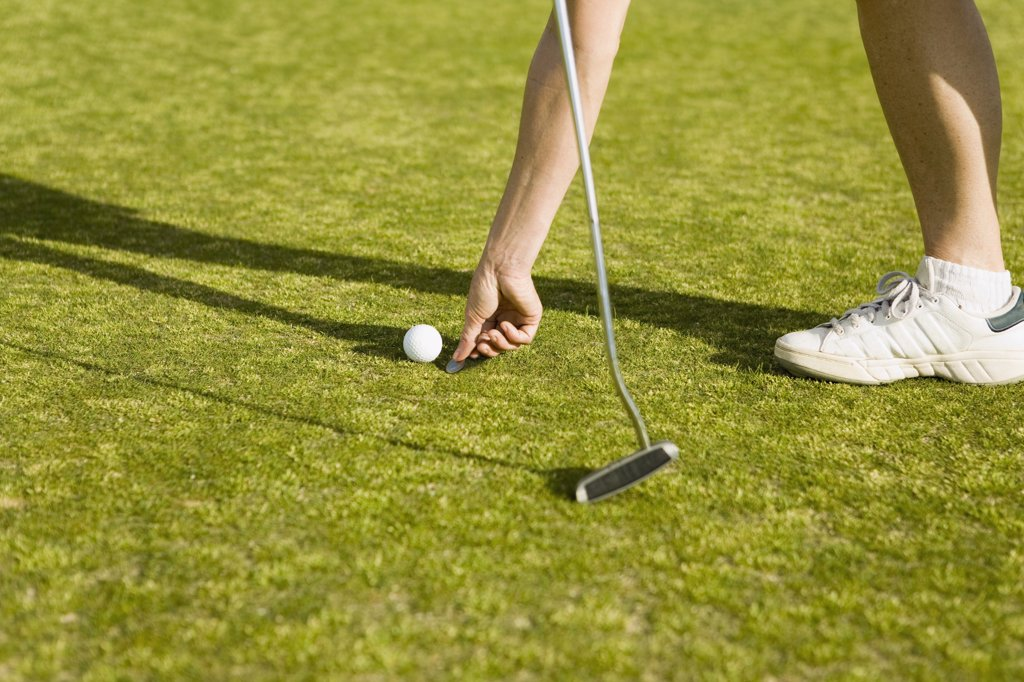Detail of a golfer marking the ball's position with a coin : Stock Photo