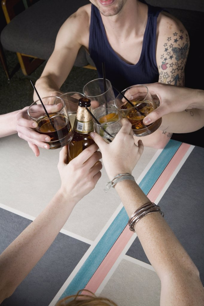 A group of friends toasting drinks at a bar : Stock Photo