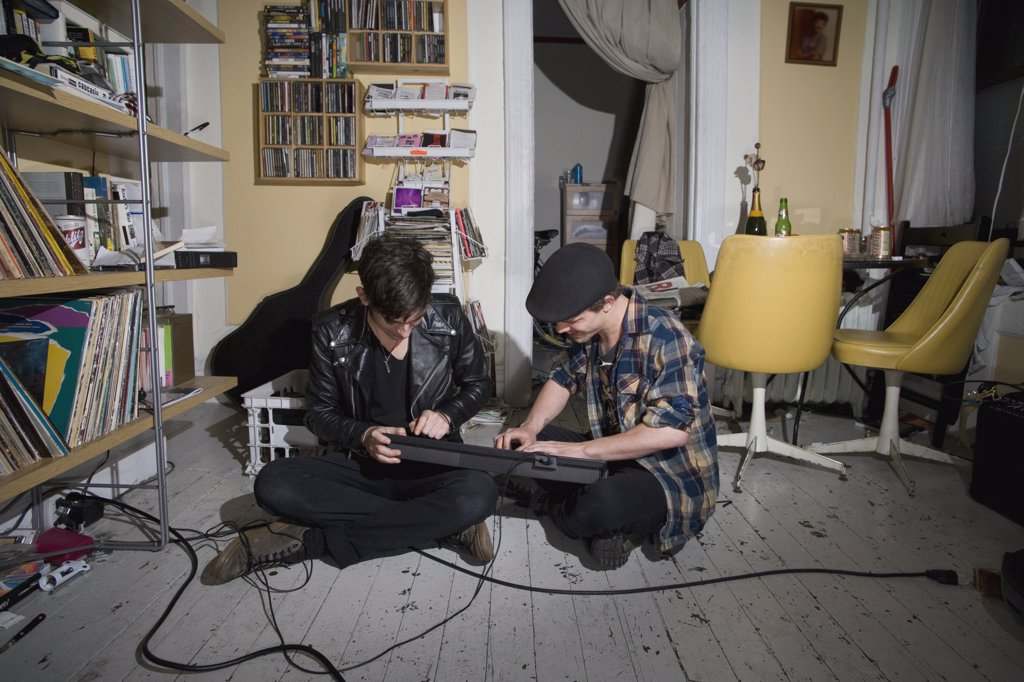 Stock Photo: 1570R-128682 Two young men sitting on the floor and playing a keyboard