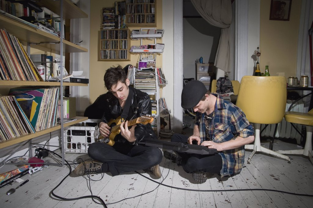 Two young men playing instruments in their living room : Stock Photo