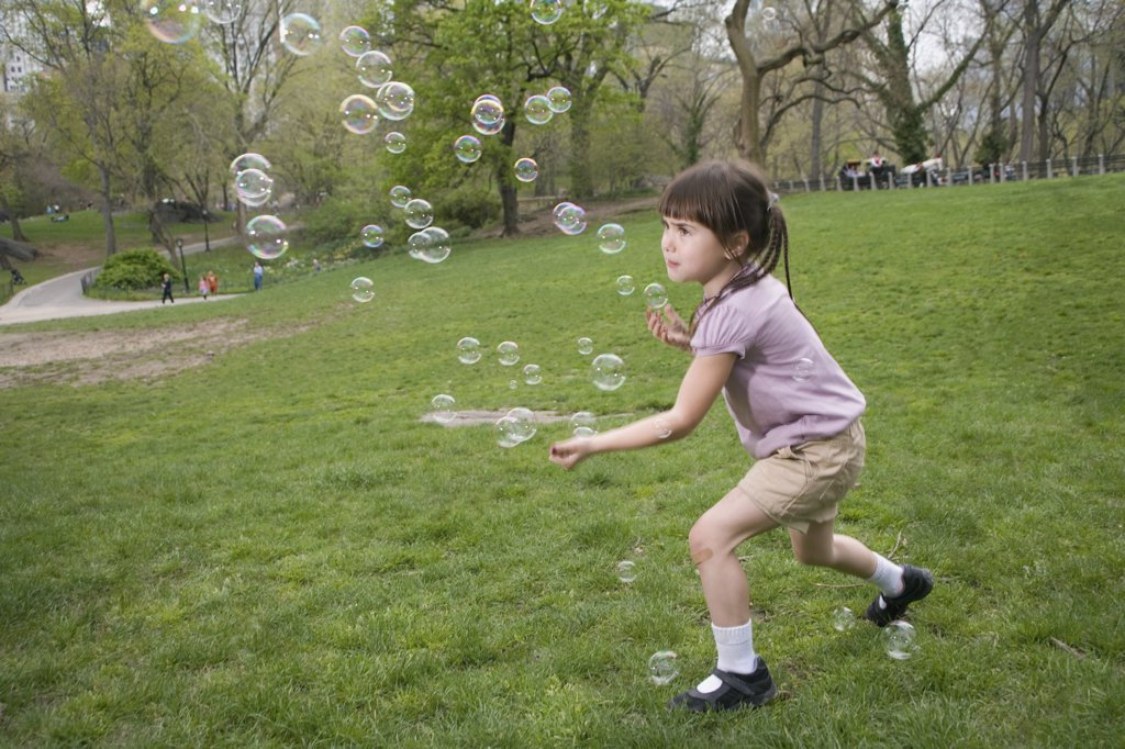 Stock Photo: 1570R-128808 A young girl catching bubbles in Central Park, New York City