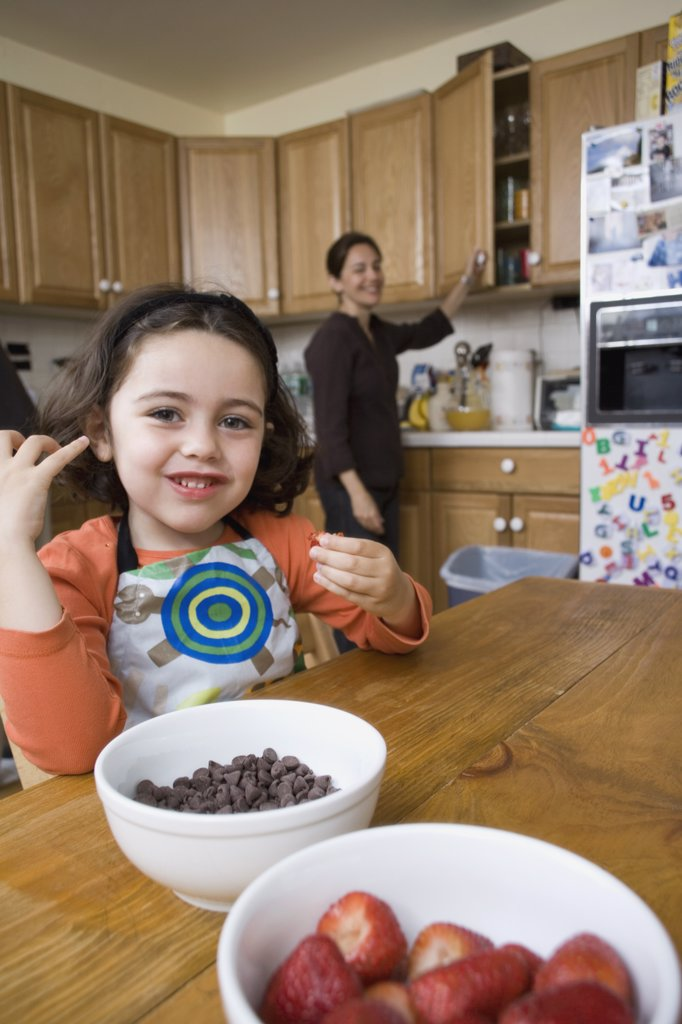 Stock Photo: 1570R-128887 A young girl sitting at a kitchen table and her mother standing behind