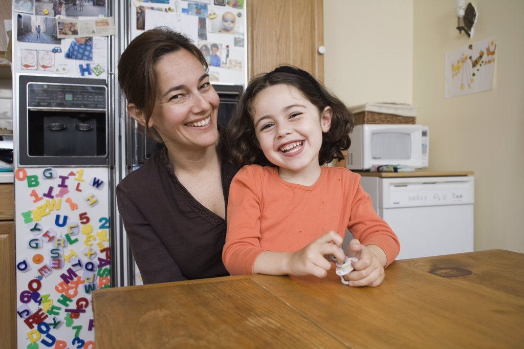 Stock Photo: 1570R-128900 Portrait of a mother and daughter sitting at a kitchen table