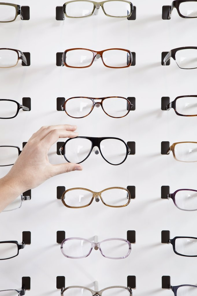 A human hand choosing a pair of glasses in an eyewear store : Stock Photo