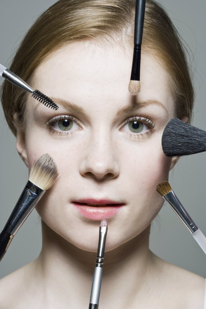 Stock Photo: 1570R-129432 A woman with various make-up brushes applying make-up to her face