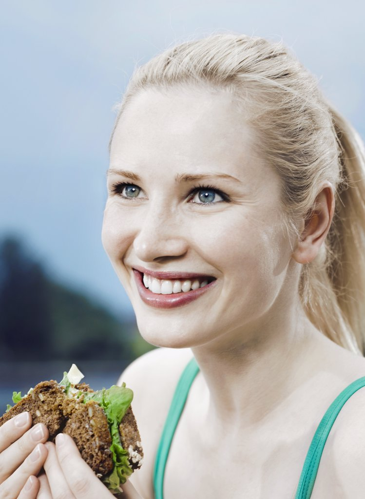 Stock Photo: 1570R-129569 A woman eating a sandwich on 7-grain bread