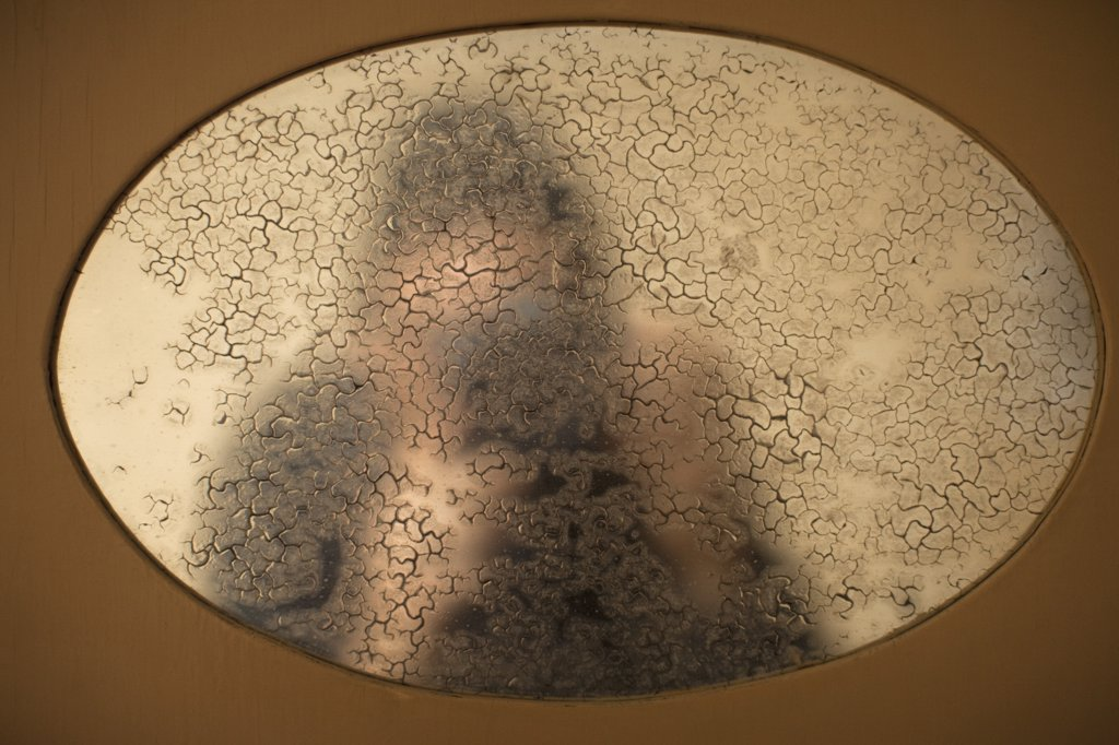 Stock Photo: 1570R-129627 Reflection in an old mirror of a person taking a photograph