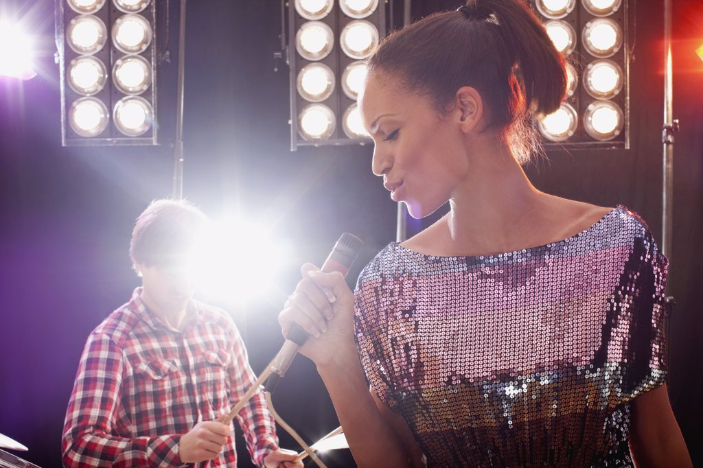 Stock Photo: 1570R-129703 A woman singer accompanied by a man on drums performing on stage
