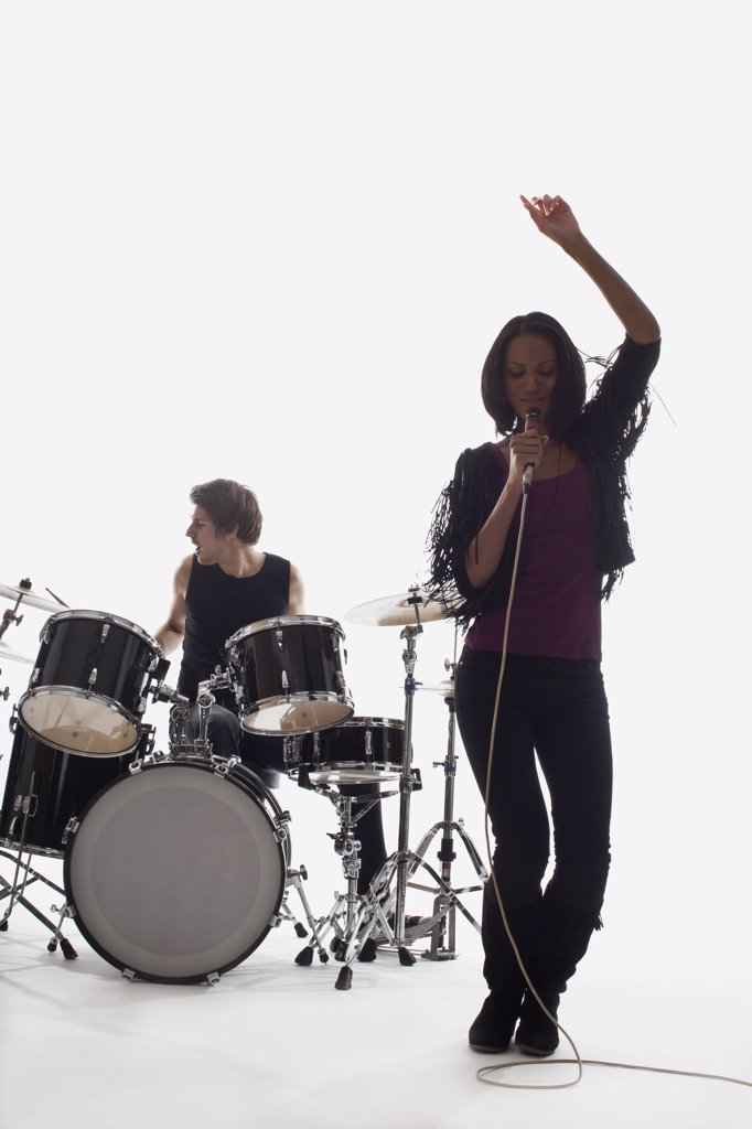 A female singer and a drummer performing, studio shot, white background, back lit : Stock Photo