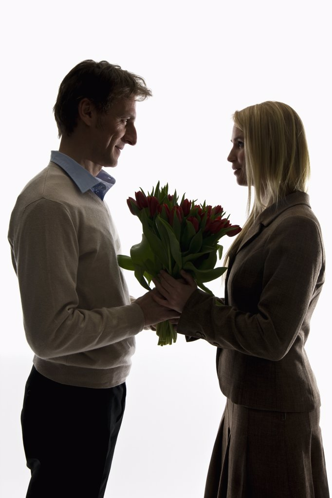A man giving a bouquet of tulips to his girlfriend : Stock Photo