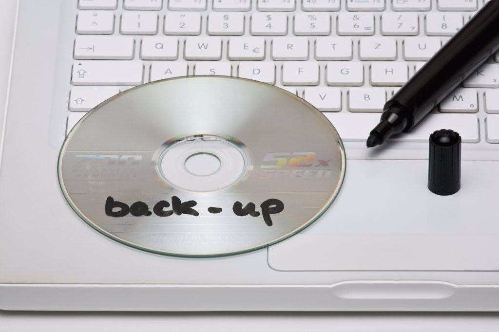 Stock Photo: 1570R-129858 Detail of a back-up disc and a marker on a laptop