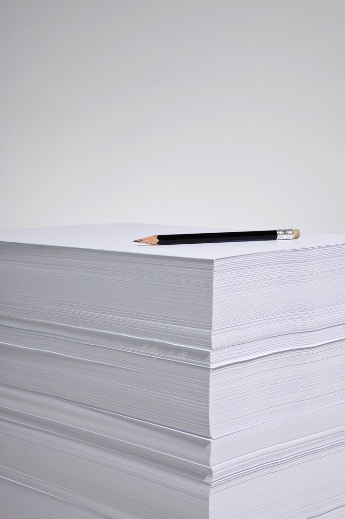 A pencil on a stack of paper : Stock Photo