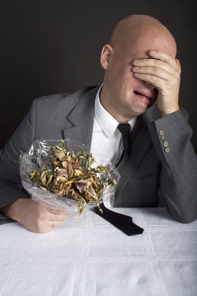 Stock Photo: 1570R-130001 A well-dressed man holding a bouquet of dead flowers and crying
