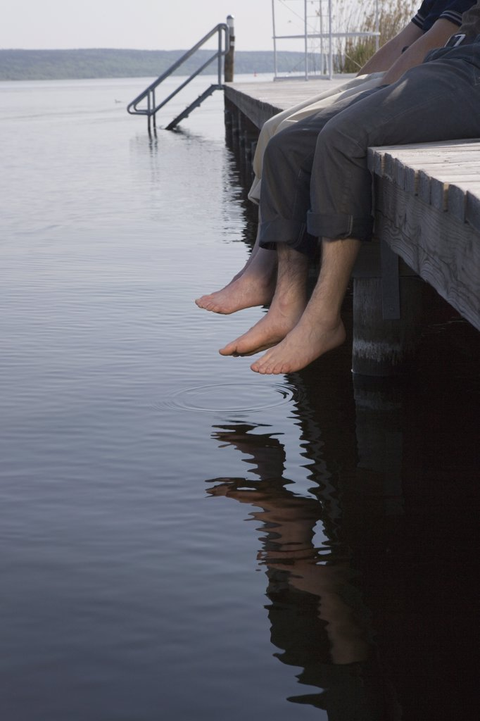 Two men sitting on jetty by lake : Stock Photo
