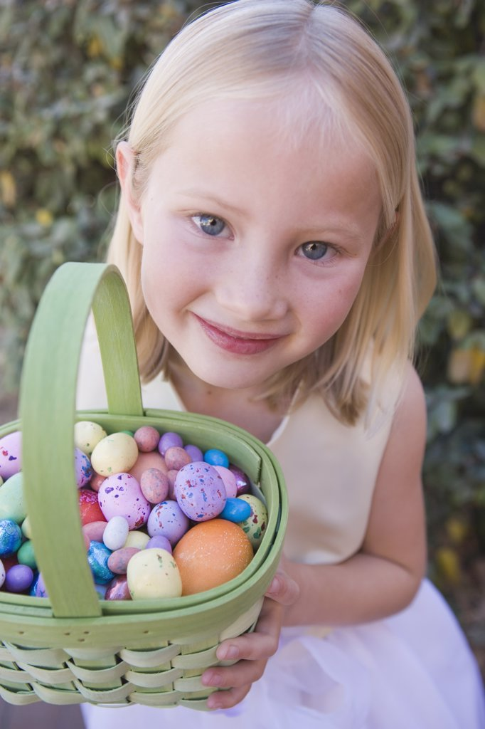 Young girl holding basket full of Easter eggs : Stock Photo