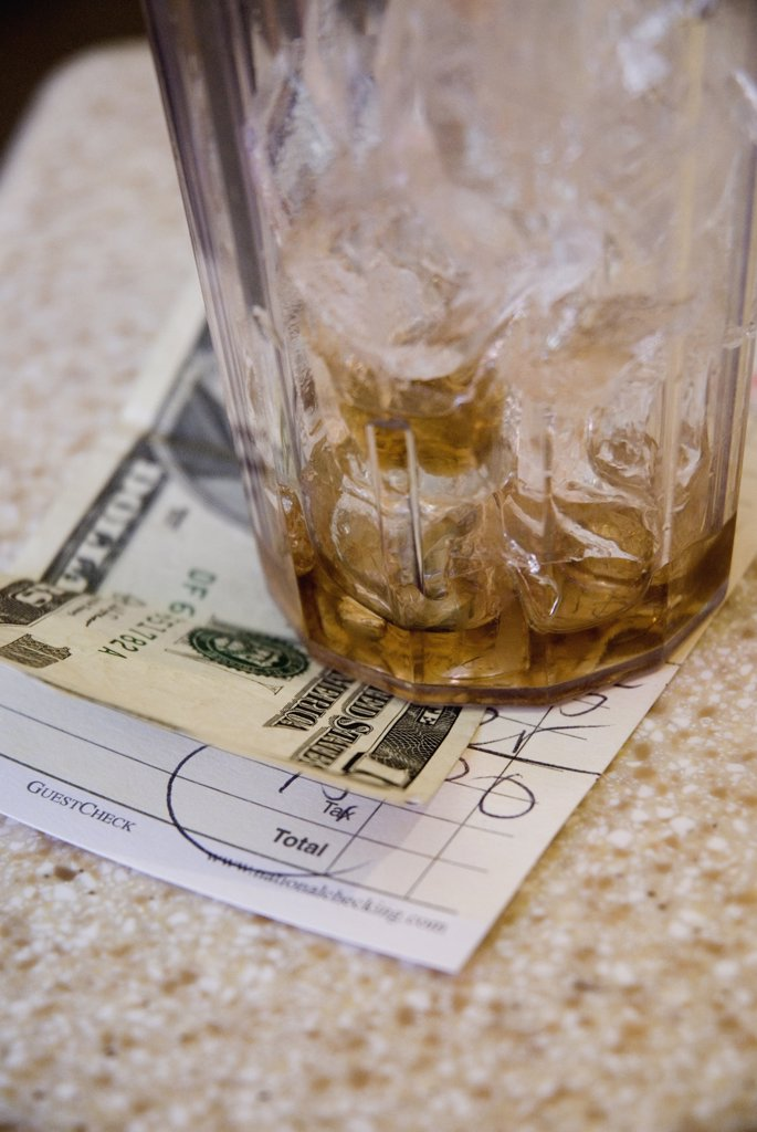 Stock Photo: 1570R-130321 A glass of ice and tip on a restaurant bill