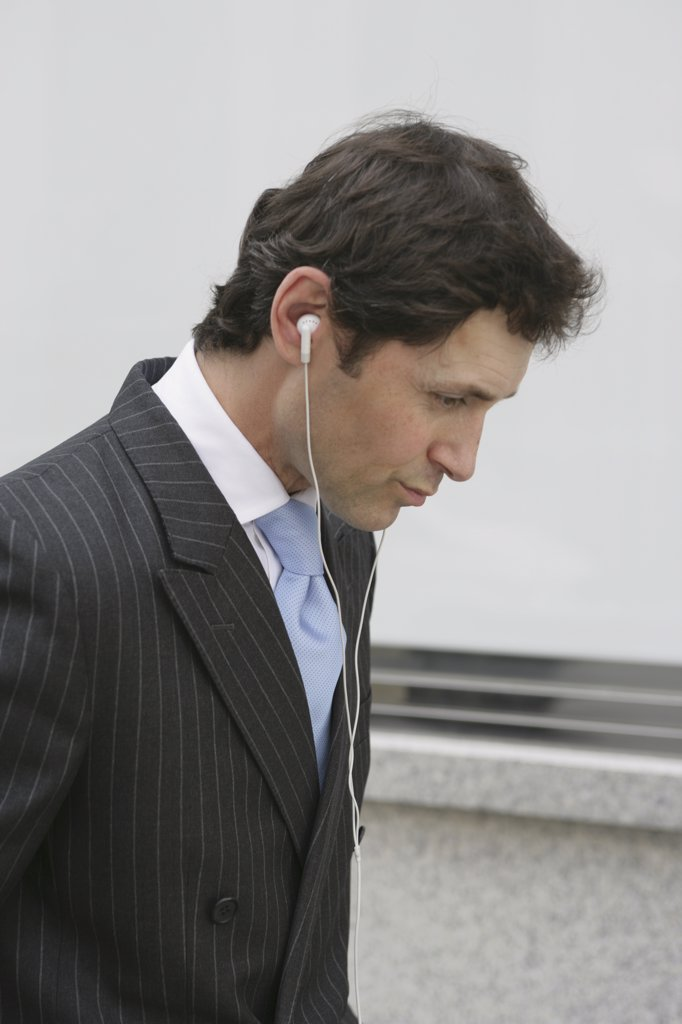 An English businessman listening to headphones : Stock Photo
