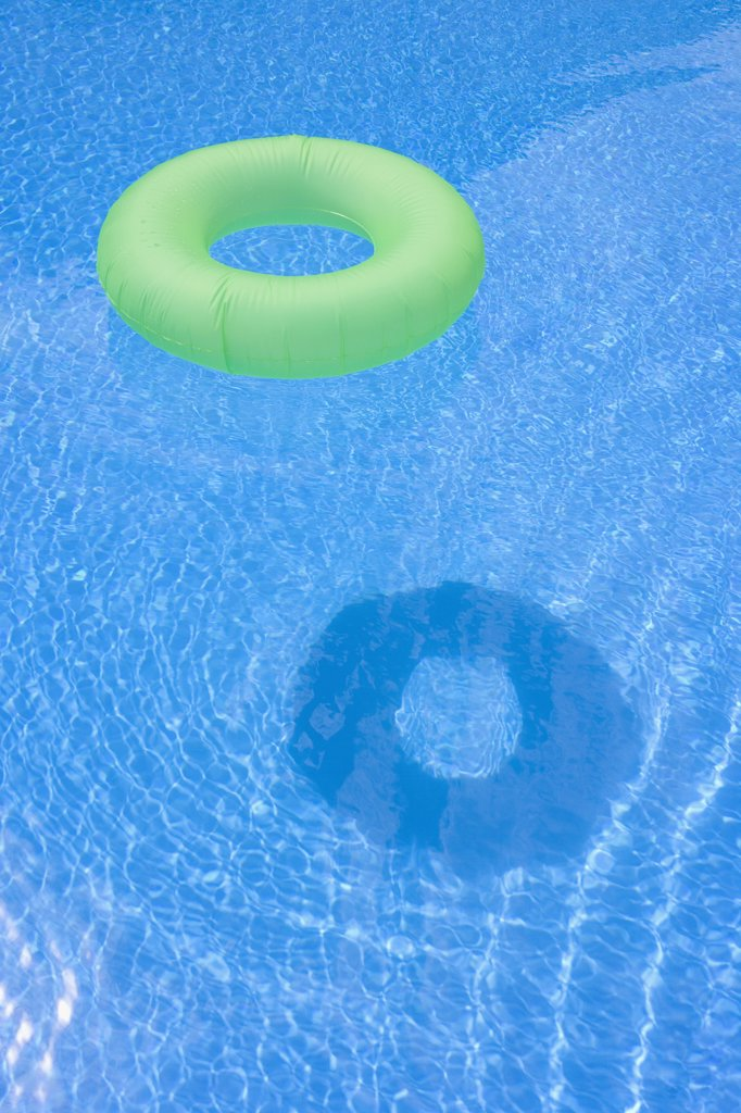 An inflatable ring floating in a swimming pool : Stock Photo