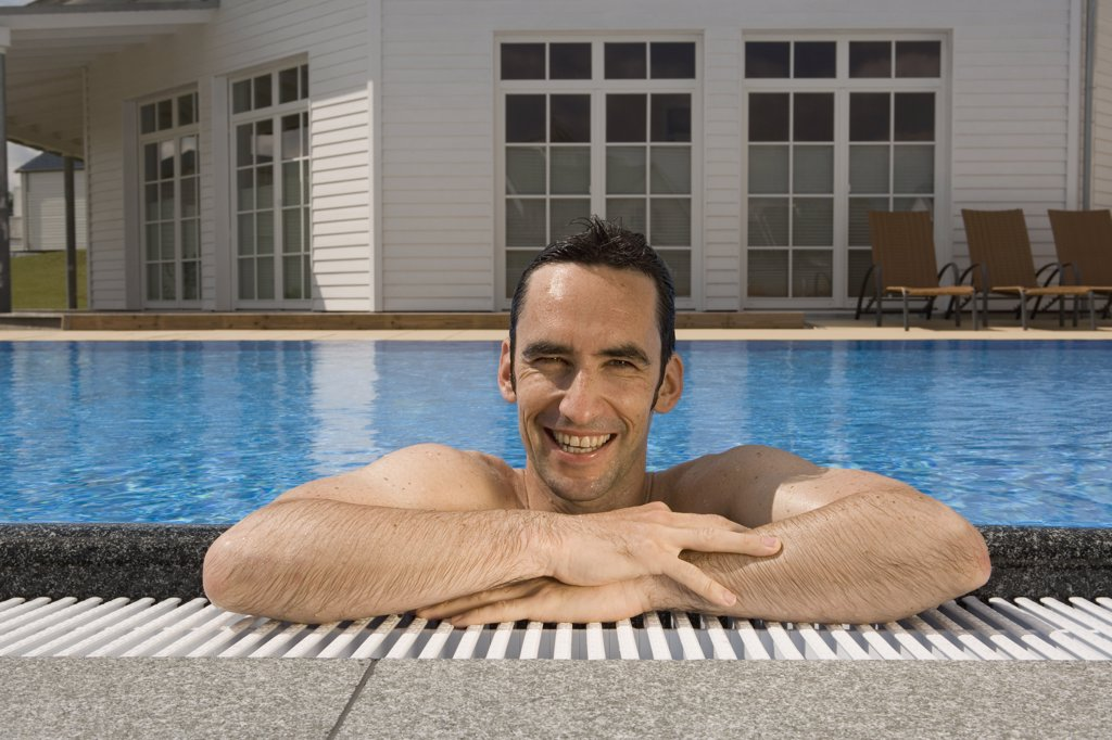 A man relaxing in a swimming pool : Stock Photo