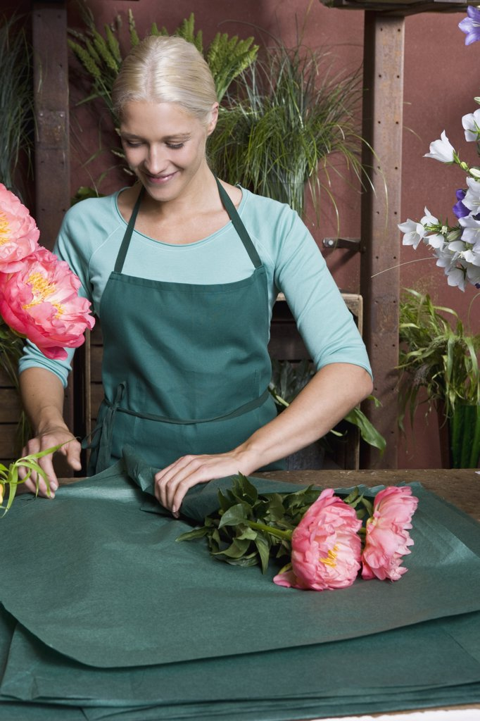A florist wrapping up a bunch of flowers : Stock Photo