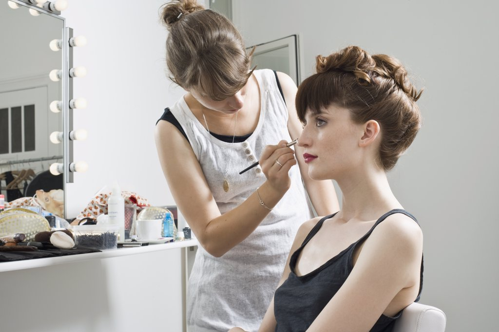A make-up artist applying make-up on a model : Stock Photo