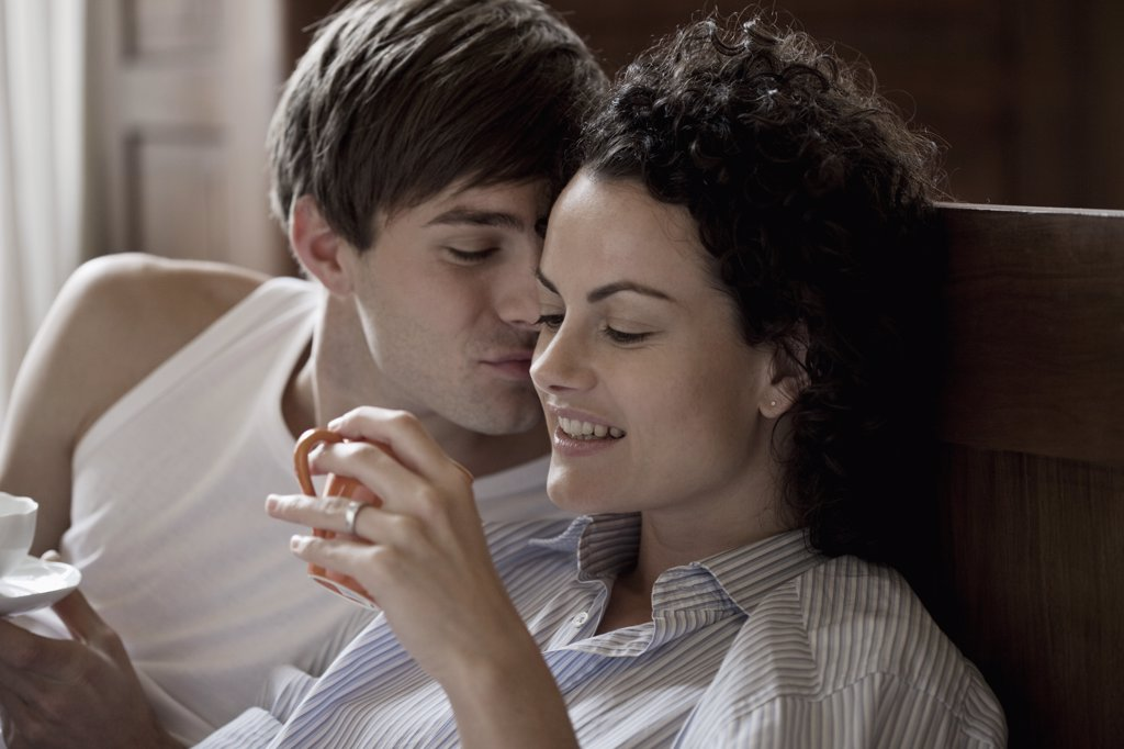 Stock Photo: 1570R-131431 A couple sitting up in bed on a morning