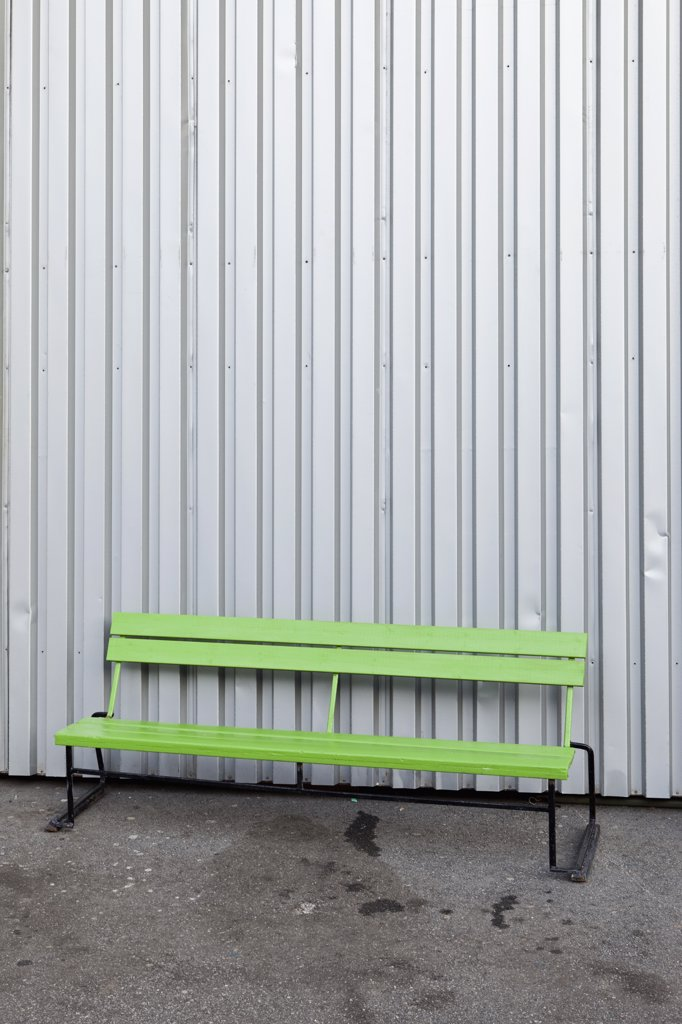 A green bench in front of a steel building : Stock Photo