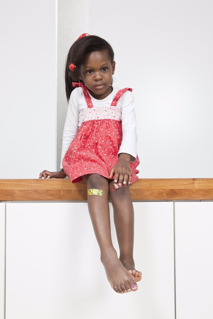 Stock Photo: 1570R-131675 A young girl with a bandage on each knee