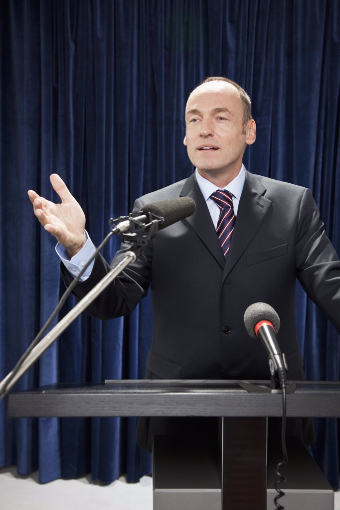 Stock Photo: 1570R-131695 A man in a suit gesturing at a lectern