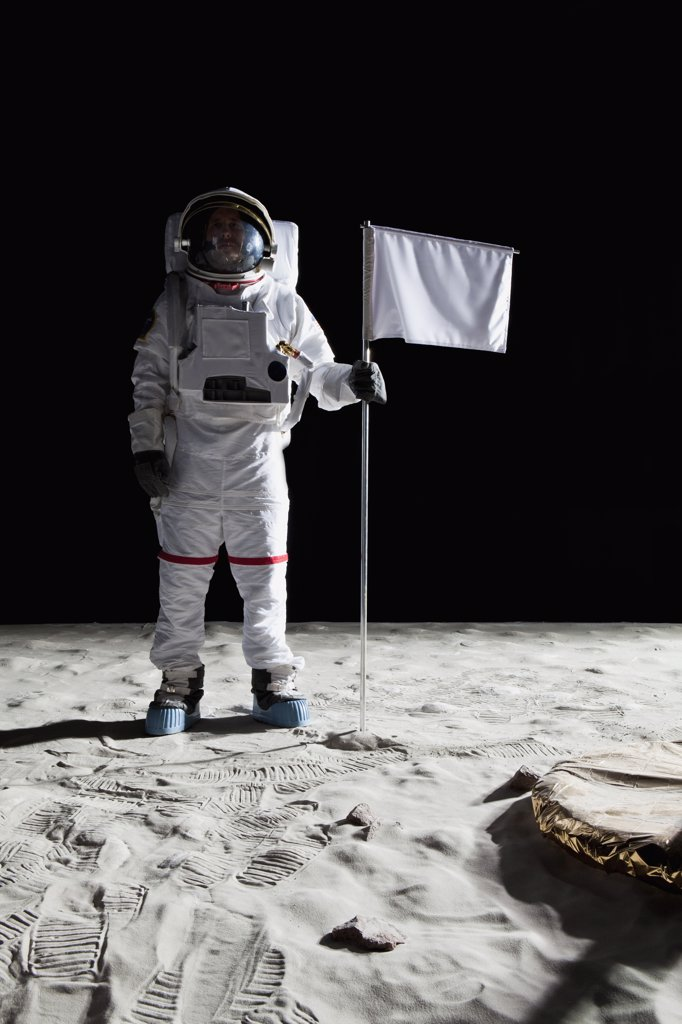 Stock Photo: 1570R-131956 An astronaut standing next to a white flag