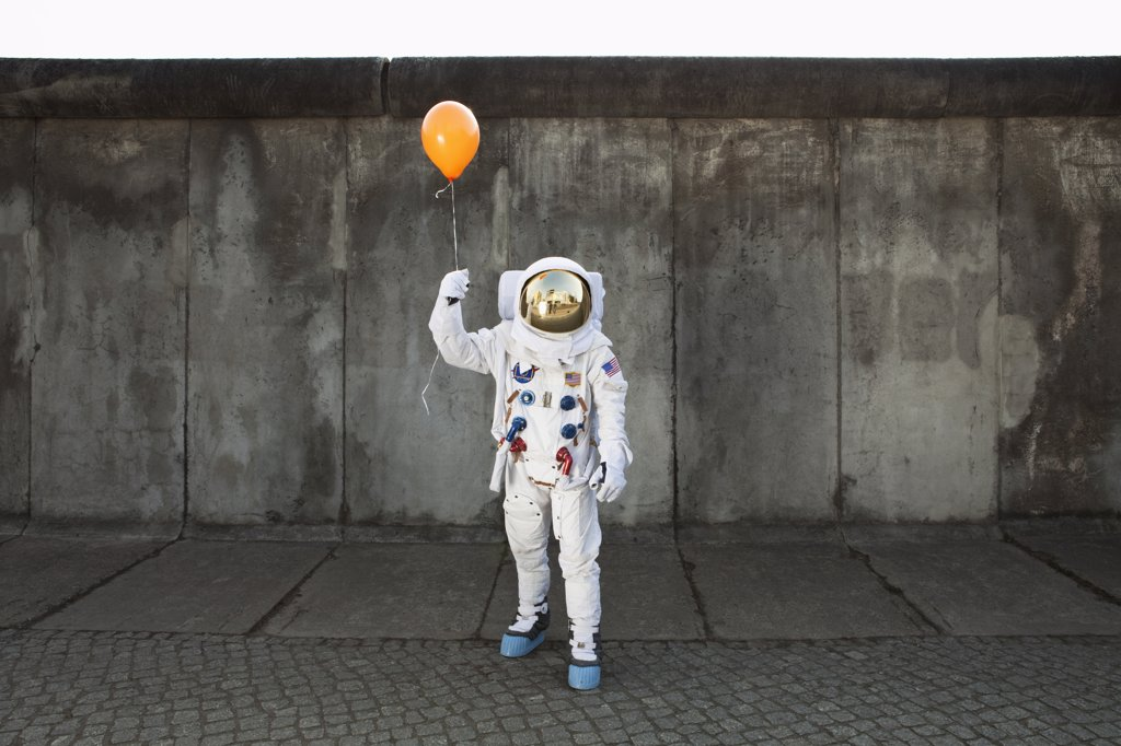 An astronaut on a city sidewalk holding a balloon : Stock Photo