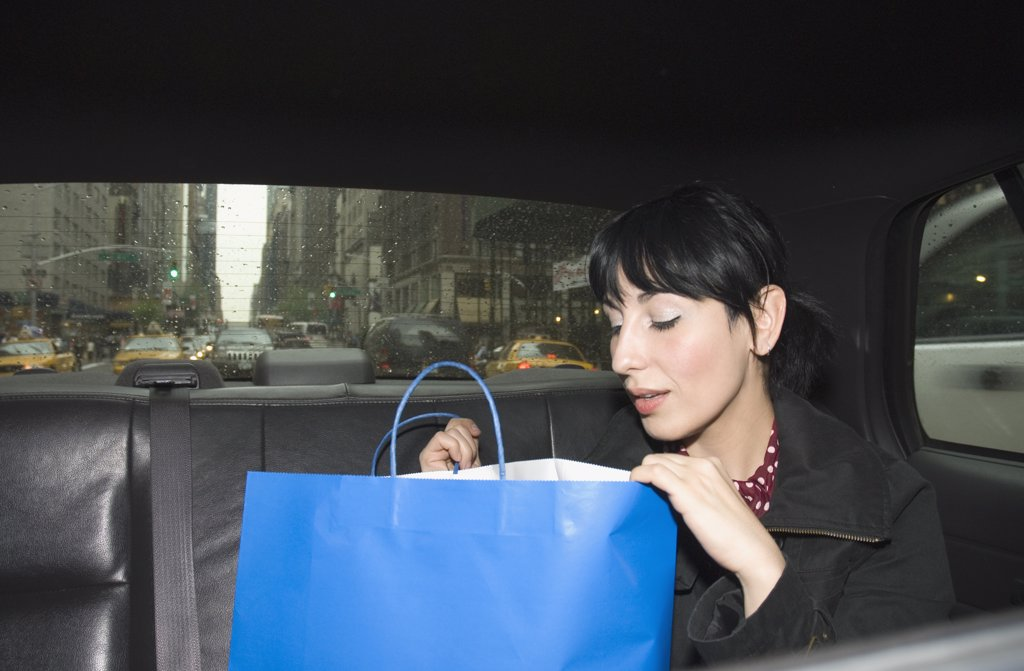 Stock Photo: 1570R-132267 Young woman looking inside shopping bag in a taxi, New York City