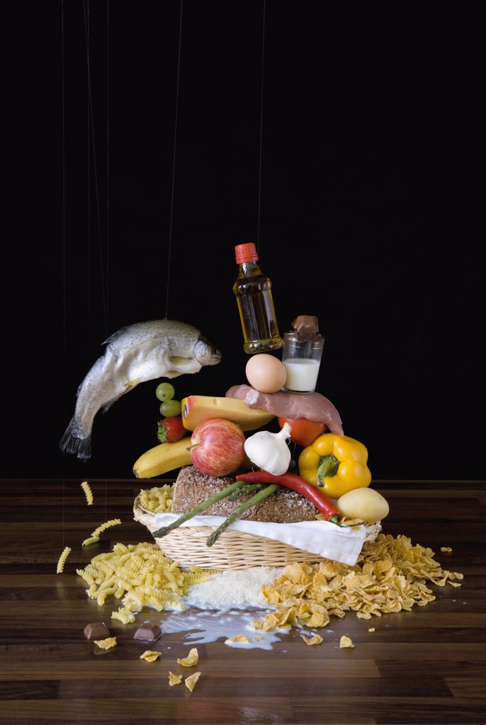 Stock Photo: 1570R-132342 Assortment of raw food stacked up in basket on table