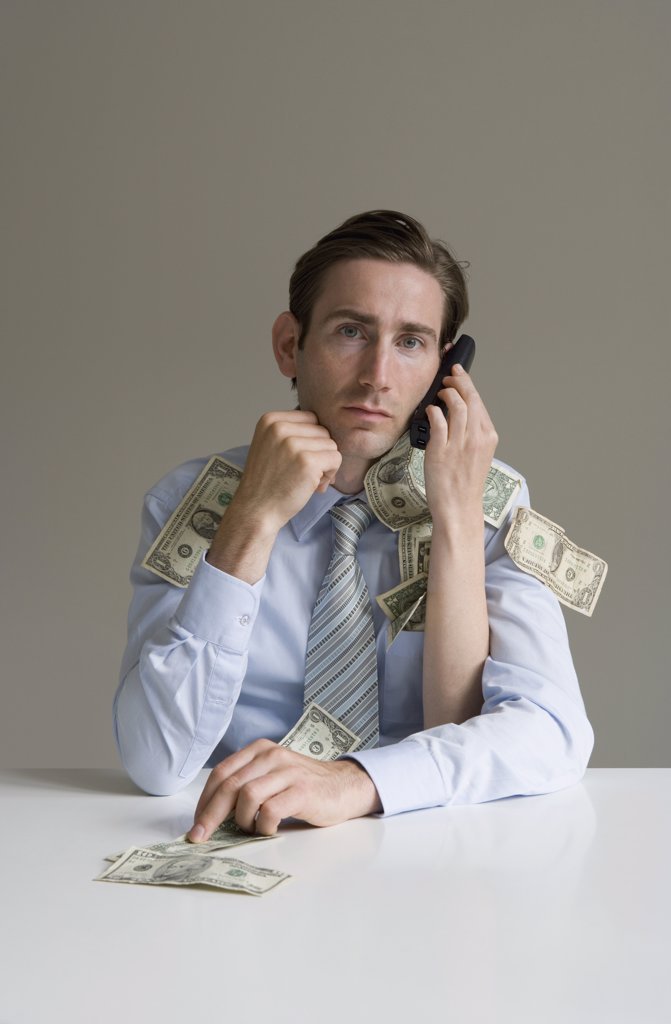 Businessman using telephone covered in money : Stock Photo