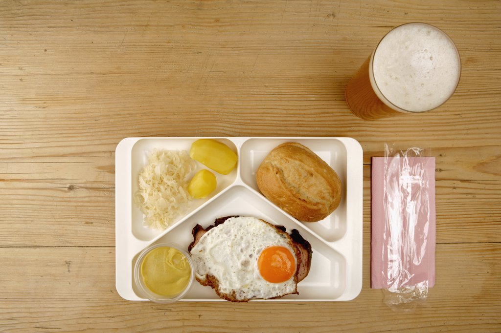 Tray with egg, sausage, sauerkraut, potato and bread next to glass of beer : Stock Photo