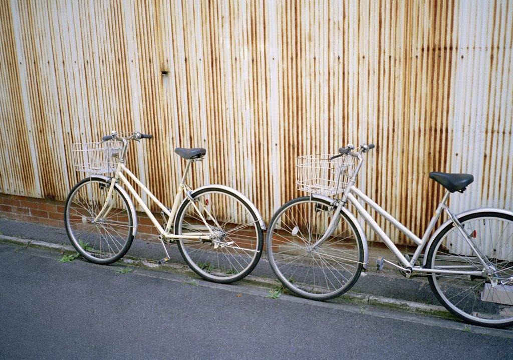 Two bicycles leaning on a wall : Stock Photo