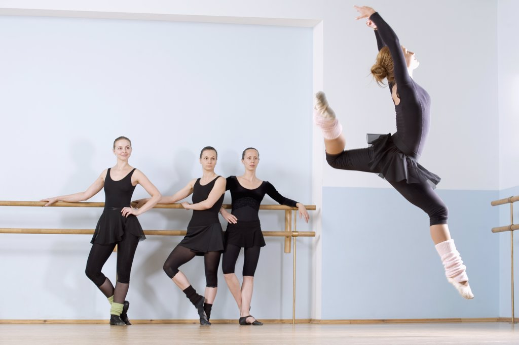 A ballerina leaping through the air as three other women look on : Stock Photo