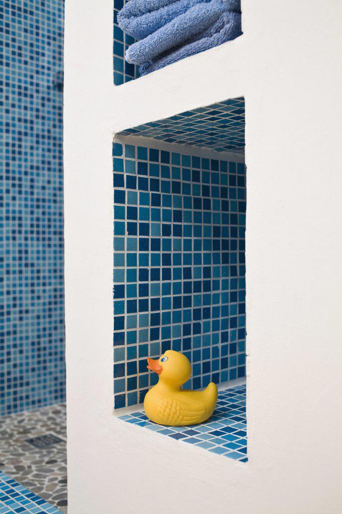 Stock Photo: 1570R-133328 A rubber duck on a tiled bathroom shelf