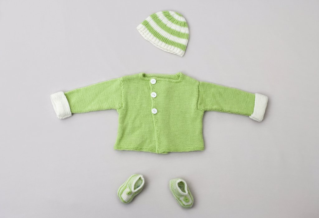 A baby sweater, knit hat and baby booties : Stock Photo