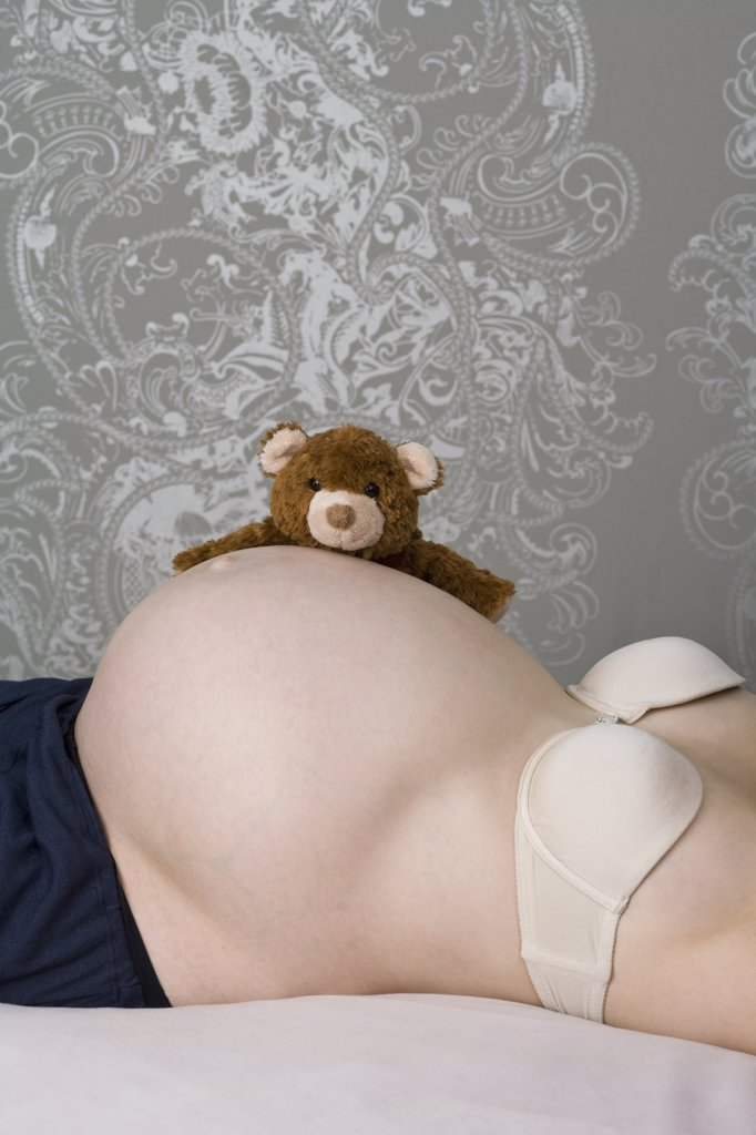 Stock Photo: 1570R-133365 A pregnant woman lying on her back with a teddy bear on her stomach, midsection