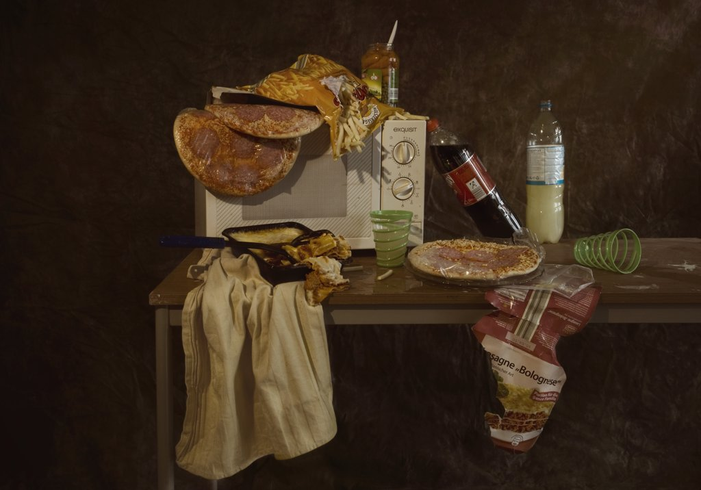Stock Photo: 1570R-133403 A table with a microwave and various frozen pizzas and frozen lasagna, still life