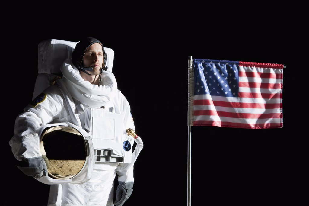 An astronaut holding his helmet standing next to an American flag, portrait : Stock Photo