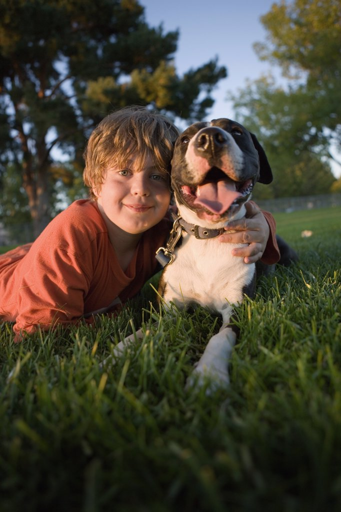 Portrait of a boy lying on grass with a dog : Stock Photo