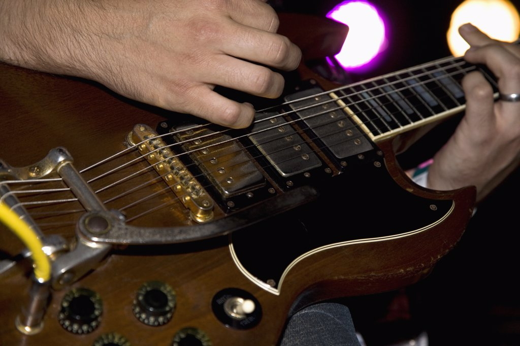 A man playing an electric guitar, close up of hands : Stock Photo