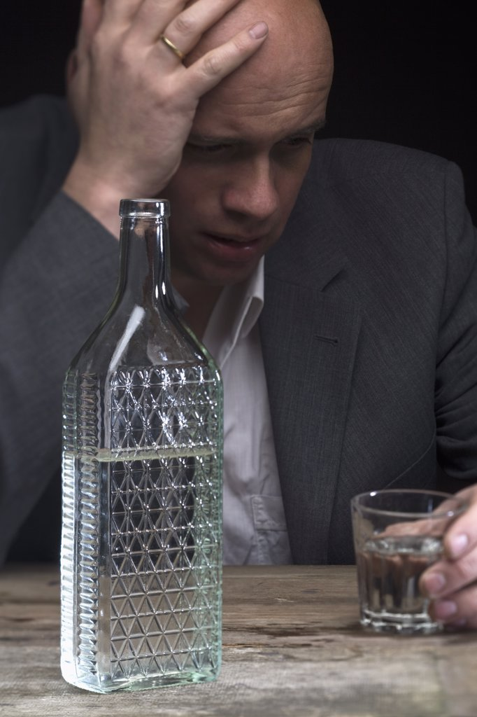 Stock Photo: 1570R-133841 A drunk and depressed businessman holding a glass of vodka