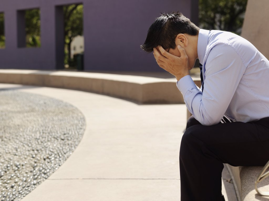 Stock Photo: 1570R-133932 A distraught businessman with his head in hands