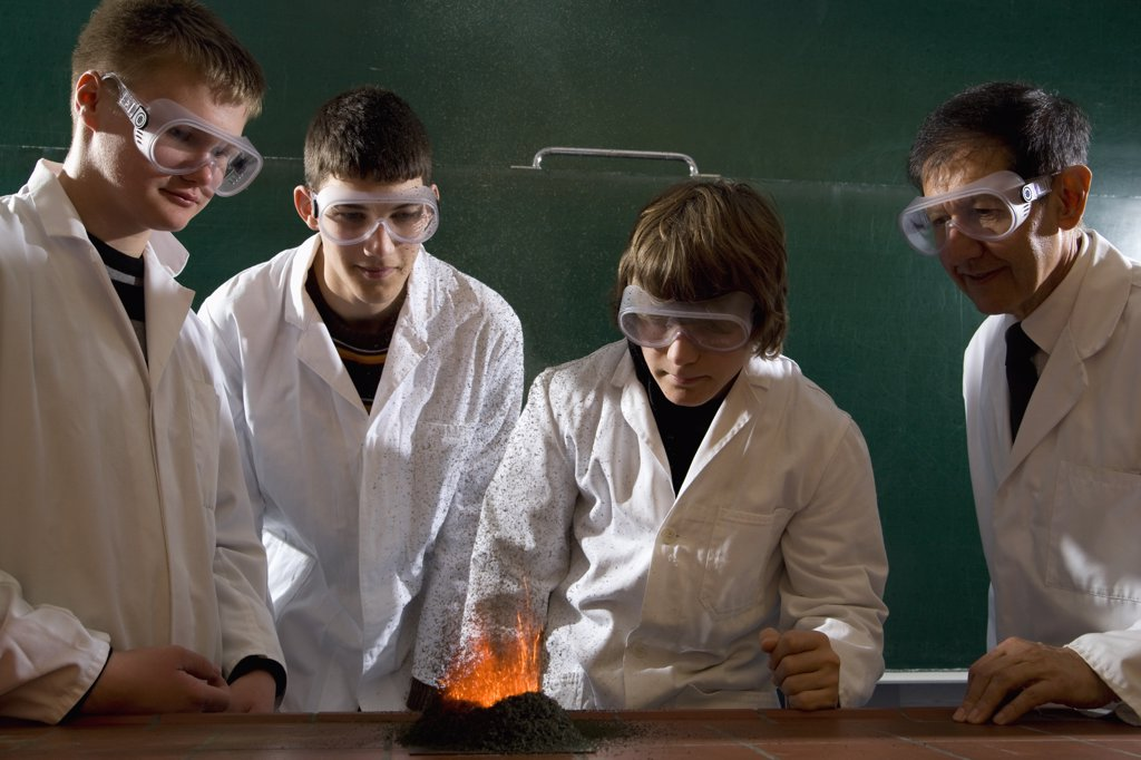 Stock Photo: 1570R-134007 A teacher supervising students doing a chemistry experiment with lit gunpowder