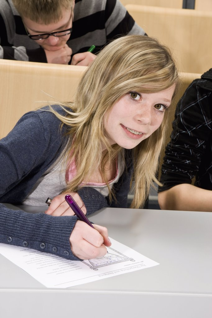 Portrait of a teenager doing a worksheet in class, smiling at camera : Stock Photo